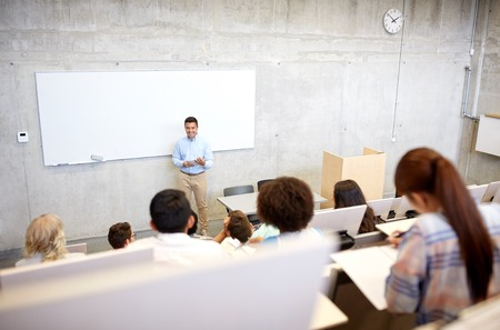 education, high school, university, teaching and people concept - group of international students and smiling teacher with papers standing at white board at lecture