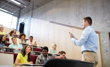 教育、高校、大学、教育、人々 コンセプト - 留学生と講義でホワイト ボードでタブレット pc コンピューターに立っている教師のグループ