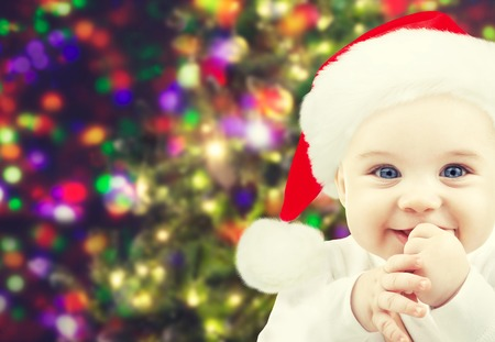christmas, babyhood, childhood and people concept - happy baby in santa hat over holidays lights background photo