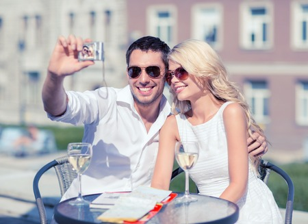 couple dating: summer holidays and dating concept - couple taking photo in cafe in the city