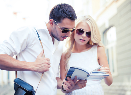 summer holidays, dating and tourism concept - couple with tourist book in the city Stock Photo