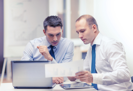 looking at computer: business, technology and office concept - two businessmen with laptop, tablet pc computer and papers having discussion in office Stock Photo