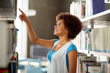 books library: education, high school, university, learning and people concept - happy smiling african american student girl pointing finger to book on shelf at library