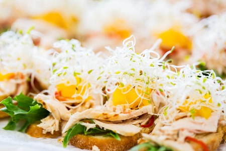 junkfood: food, junk-food, catering and unhealthy eating concept - close up of canape or sandwiches on serving tray