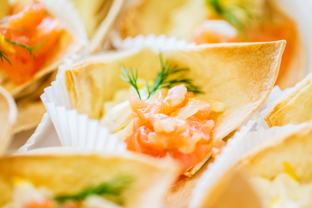 cornet: food, catering and unhealthy eating concept - close up of dough cornet with salmon fish filling Stock Photo