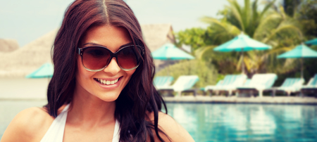 hispanic girl: summer vacation, tourism, travel, holidays and people concept -face of smiling young woman with sunglasses over beach and swimming pool background