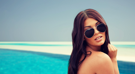 summer vacation, tourism, travel, holidays and people concept -face of young woman with sunglasses over beach and swimming pool background Stock Photo