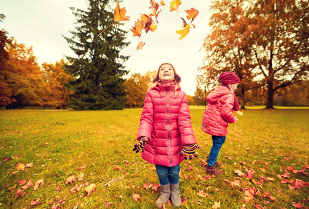 childhood, leisure, friendship and people concept - group of happy little girl playing with autumn maple leaves and having fun in park Stock Photo