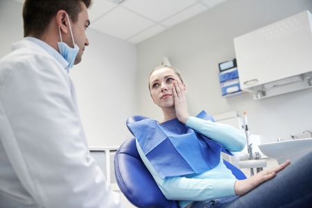 complain: people, medicine, stomatology and health care concept - woman patient talking to male dentist and complain of toothache at dental clinic office
