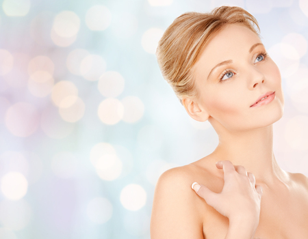 woman looking: beauty, people and bodycare concept - beautiful young woman face and hands over blue holidays lights background Stock Photo