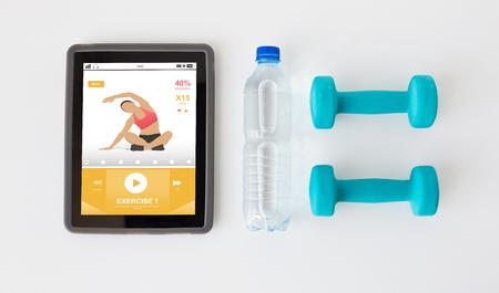 sport, mode de vie sain, de remise en forme, le concept de la technologie et des objets - à proximité d'ordinateur tablette pc avec des haltères et une bouteille d'eau sur fond blanc
