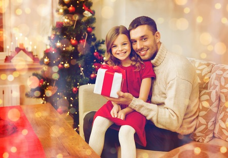 daugther: family, christmas, x-mas, winter, happiness and people concept - smiling father and daughter holding gift box Stock Photo