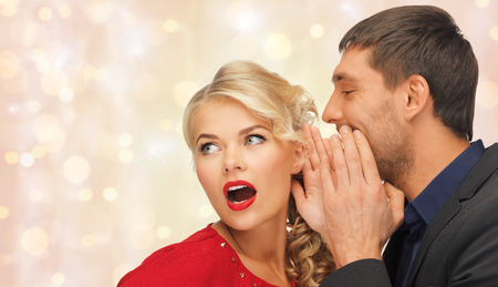 scandalous: people, communication, gossiping, christmas and information concept - close up of man and woman spreading gossip over holidays lights and snow background Stock Photo