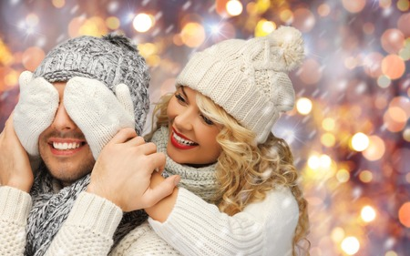 christmas winter: people, christmas, holidays and new year concept - happy family couple in winter clothes playing guess who game over holidays lights and snow background