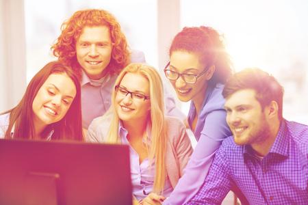 monitor de computadora: negocio, oficina, tecnología y puesta en marcha concepto - sonriente equipo de negocios que buscan en el monitor del ordenador en la oficina