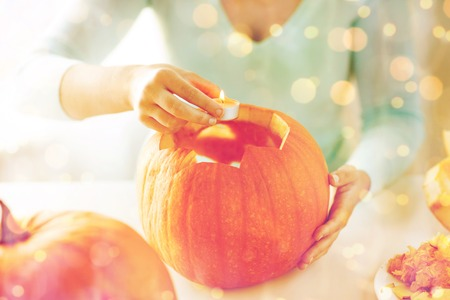celebration smiley: holidays, halloween, decoration and people concept - close up of woman with pumpkins at home Stock Photo