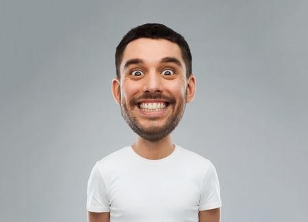 expressie en mensen concept - lachende man met grappig gezicht over grijze achtergrond (cartoon stijl karakter met grote kop) Stockfoto