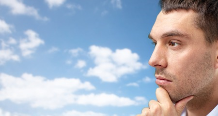 face work: business, people and work concept - close up of businessman face over blue sky and clouds background Stock Photo