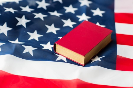 nationalism: independence day, patriotism, civil rights, cultural values and nationalism concept - close up of american flag and constitution book or bible
