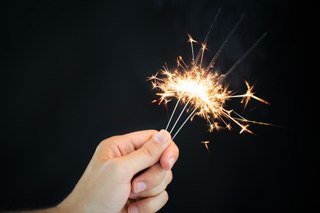 pyrotechnics: christmas, holidays, new year party and pyrotechnics concept - male hand holding sparklers or bengal light burning over black background Stock Photo