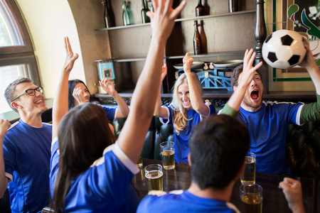 sports bar: sport, people, leisure, friendship and entertainment concept - happy football fans or friends drinking beer and celebrating victory at bar or pub Stock Photo