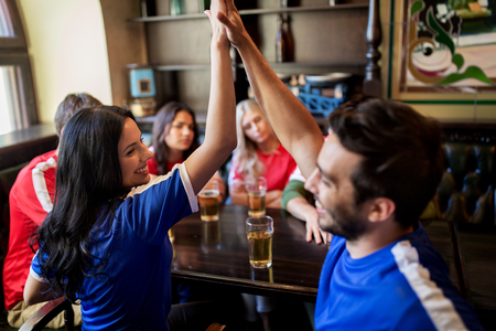 sports bar: sport and entertainment concept - happy football fans or friends drinking beer, making high five and celebrating victory at bar or pub, supporting two teams with different shirt color
