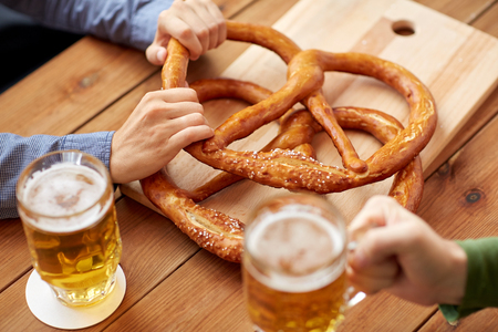 people, leisure and drinks concept - close up of men drinking beer with pretzels at bar or pub Stock Photo
