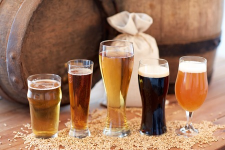 brewery, drinks and alcohol concept - close up of old beer barrel, glasses and bag with malt on wooden table Stock Photo