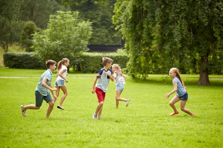 friendship, childhood, leisure and people concept - group of happy kids or friends playing catch-up game and running in summer park Stock Photo