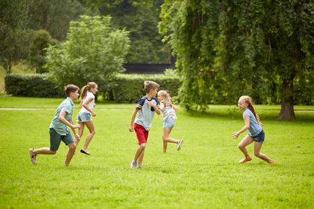 vriendschap, jeugd, vrije tijd en mensen concept - groep gelukkige jonge geitjes of vrienden te spelen catch-up spel en lopen in de zomer park Stockfoto