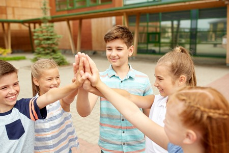 primary education, friendship, childhood and people concept - group of children or students making high five at school yard