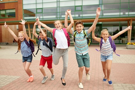 niños saliendo de la escuela: la educación primaria, la amistad, la infancia y las personas concepto - grupo de estudiantes de la escuela primaria felices con mochilas corriendo y agitando las manos al aire libre Foto de archivo