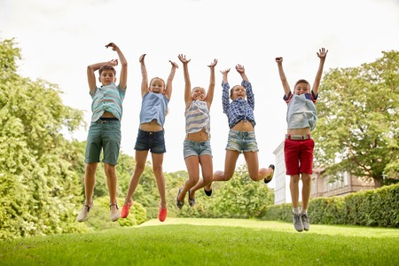 friendship, childhood, leisure and people concept - group of happy kids or friends jumping up and having fun in summer park