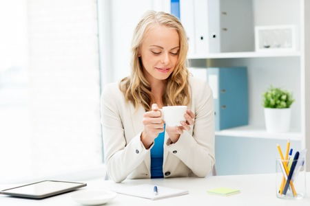 business, education and people concept - happy young businesswoman or student girl drinking coffee at office