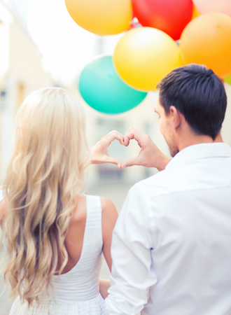 couple dating: summer holidays, celebration and dating concept - couple with colorful balloons making heart shape in the city