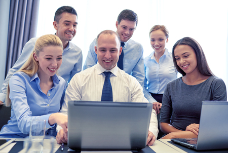 team communication: business, people, technology and communication concept - smiling business team with laptop computer making video conference in office