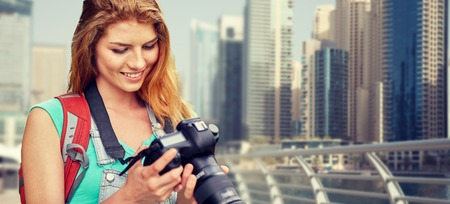 adventure, travel, tourism, hike and people concept - happy young woman with backpack and camera photographing over dubai city waterfront background