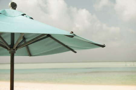blue summer sky: travel, tourism, vacation, beach and summer holidays concept - parasol over blue sky and beach