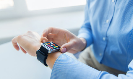 business, technology and people concept - close up of woman hands with menu icons on smart watch screen at office Stock Photo