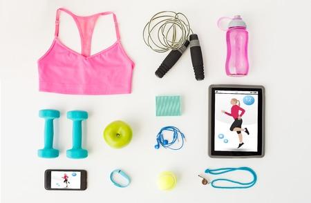 sport, fitness, gezonde levensstijl, technologie en objecten concept - close-up van de tablet-pc computer met smartphone en sport spullen op een witte achtergrond