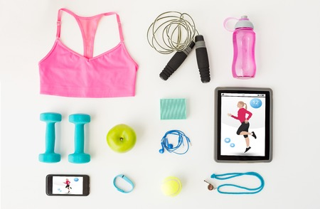 computer program: sport, fitness, healthy lifestyle, technology and objects concept - close up of tablet pc computer with smartphone and sports stuff over white background