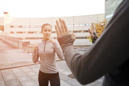 fitness, sport, mensen, het uitoefenen en martial arts concept - jonge vrouw met een trainer die zelfverdediging staking op stadsstraat Stockfoto