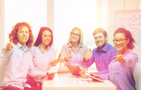 concep: business, office, gesture and startup concep - smiling creative team with table pc computers and papers showing thumbs up in office Stock Photo