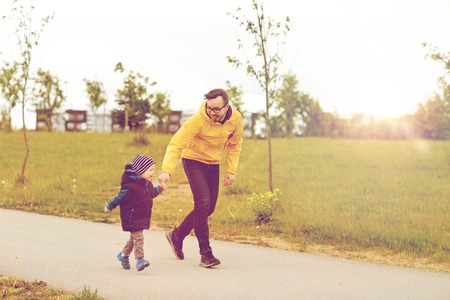 dad son: family, childhood, fatherhood, leisure and people concept - happy father and little son walking outdoors