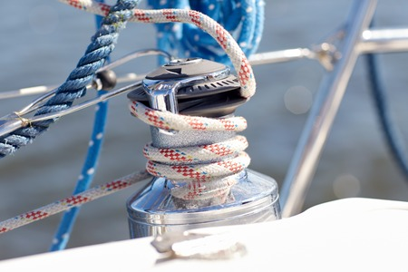 sailboat: vacation, travel, cruise and yachting concept - close up of mooring rope on sailboat or sailing yacht deck and sea