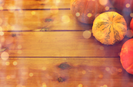 food, harvest, season and autumn concept - close up of pumpkins on wooden table at home