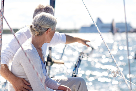 sailing, age, tourism, travel and people concept - happy senior couple pointing finger on sail boat or yacht deck floating in sea
