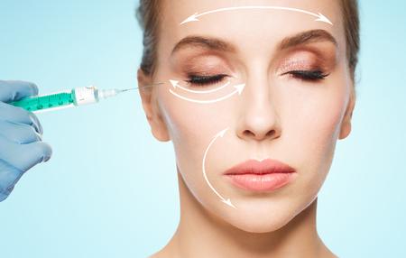 人、美容、整形手術、美容コンセプト - 美しい若い女性の顔と注射器注入をかけて青い背景と手袋で手の美容師