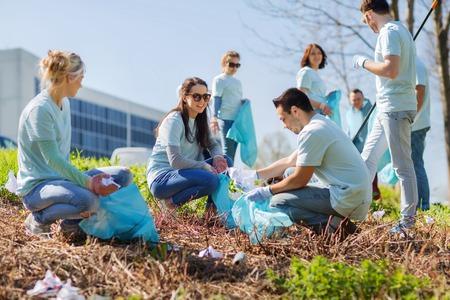 freiwilliges Engagement, Charity, Reinigung, Menschen und Ökologie-Konzept - Gruppe von glücklichen Freiwilligen mit Müllsäcken Bereich im Park Reinigung