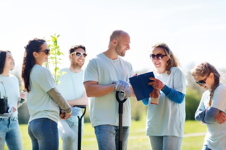 community garden: volunteering, charity, people and ecology concept - group of volunteers with clipboard planting trees in park